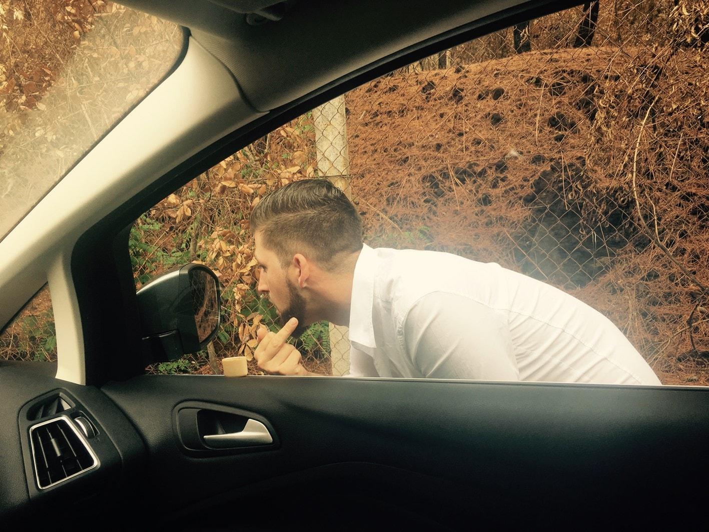 Jay Octavouj zeigt Mittelfinger beimSchminken im Autospiegel für Musikvideodreh